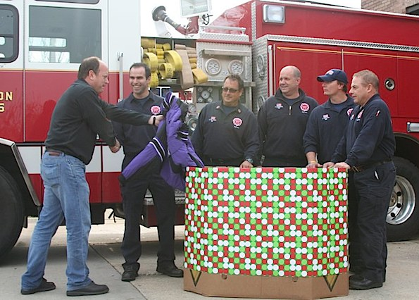 Arlington Heights firefighters receive a coat donation for their Coat Drive