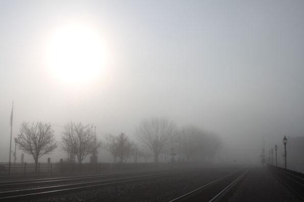 Sunrise in fog over railroad tracks