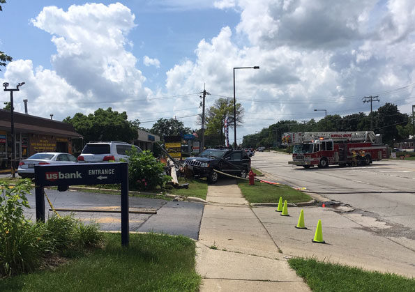 Jeep Grand Cherokee over sidewalk with broken utility pole and downed power lines