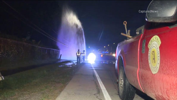 Water main geyser with Arlington Heights public works crew assessing the scene