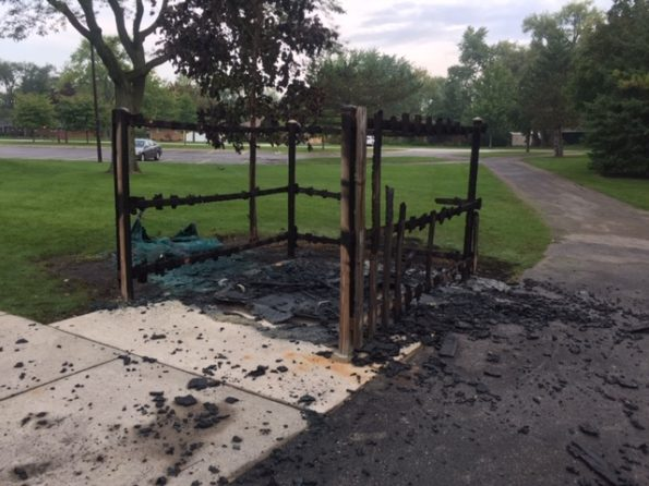Fire-damaged portable toilet, enclosure and tree at Hasbrook Park on Maude Avenue