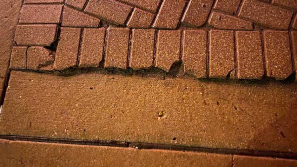 Cracked bricks at edge of corner at Northwest Highway and Arlington Heights Road
