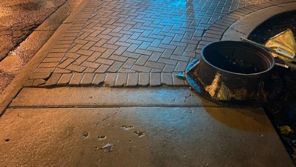 Cracked bricks and manhole piece at edge of corner at Northwest Highway and Arlington Heights Road