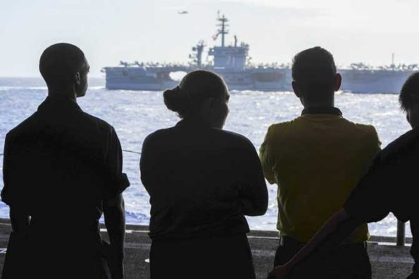 Sailors assigned to the amphibious assault ship USS America watch the aircraft carrier USS Theodore Roosevelt as it sails alongside in the Philippine Sea, Feb. 15, 2020