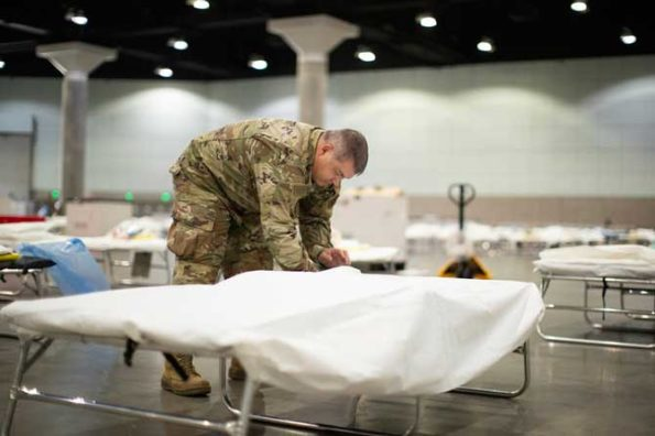 An airman with the California Air National Guard sets up a hospital bed in a medical station inside the Los Angeles Convention Center, March 29, 2020