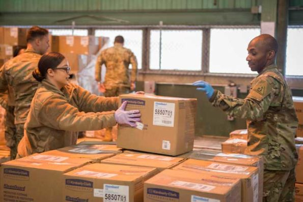 Connecticut National Guardsmen organize boxes containing personal protective equipment at a warehouse in New Britain, Conn., March 30, 2020