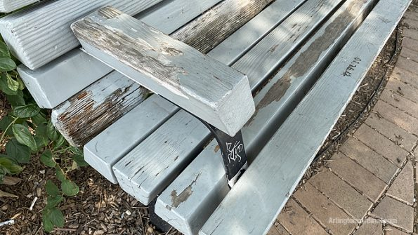 Graffiti on park bench with stripped paint and rotting wood