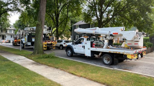 Three of at least six ComEd trucks part of preparation to install two new utility poles and restore power lines