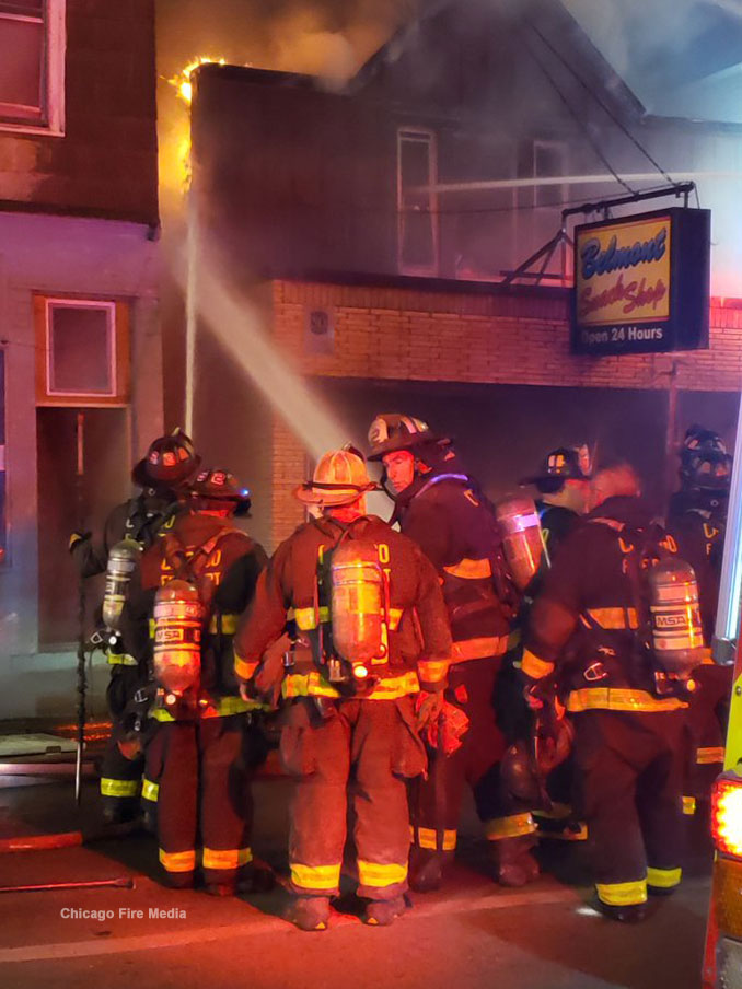 Belmont Snack Shop fire with with firefighters working to prevent the fire from spreading to the building to the left (Chicago Fire Media)