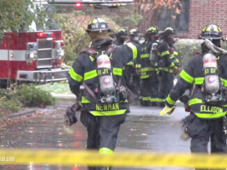 Firefighters with axes standing by t the scene of a gas main leak in Arlington Heights, Illinois