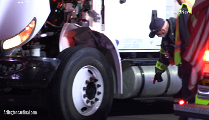 Arlington Heights firefighters inspect a saddle tank that carries diesel fuel after a pedestrian was hit by a box truck on Rand Road between Dryden Avenue and Thomas Street in Arlington Heights