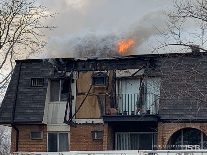 Fire showing from the roof after it burned off a section of vertical mansard roof at condo apartment fire in Palatine (PHOTO CREDIT: Lance Neuses)