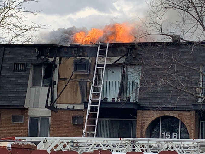 Significant fire showing from the roof after it burned off a section of vertical mansard roof at condo apartment fire in Palatine (PHOTO CREDIT: Lance Neuses)