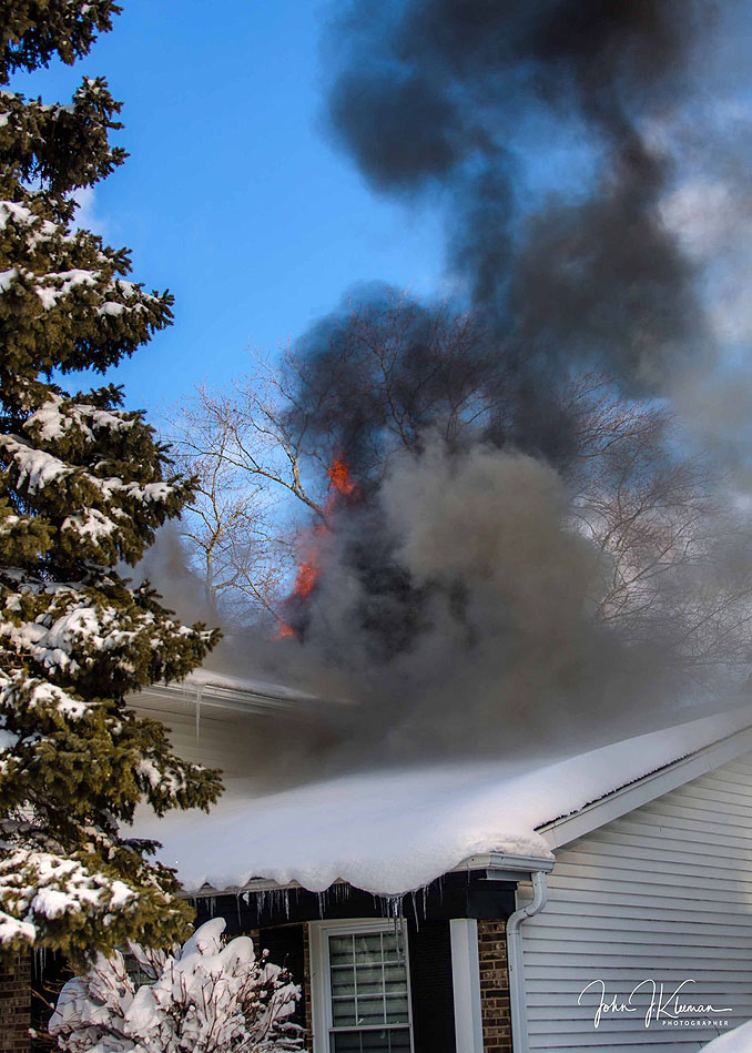 Smoke and flames showing from the back of a house at a house fire on Patton Drive in Buffalo Grove (PHOTO CREDIT: J Kleeman)