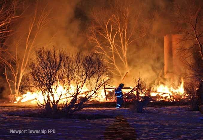 Firefighter walks across property in front of burning barn on Kazmer Road in Newport Township (SOURCE: Newport Township Fire Protection District)