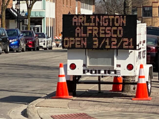 Portable electronic sign board announces Arlington Alfresco opens March 12, 2021.