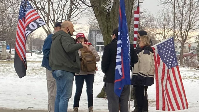 People with Pro-Trump items at the northwest corner of Golf Road and Meacham Road at a demonstration on January 17, 2021 after counter protesters had left the area