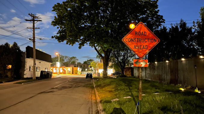 Cross traffic warning sign for ROAD CONSTRUCTION AHEAD on westbound George Street east of Arlington Heights Road in Arlington Heights, May 11, 2021