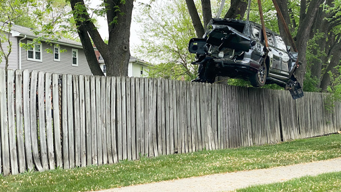 A Toyota SUV lifted over a fence by Hillside Service using a rotator crane tow truck on Monday, May 17, 2021