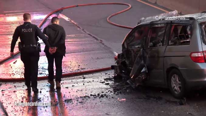 Wrong way driver is led in handcuffs past the destroyed and burned up minivan he was allegedly driving the westbound in the eastbound lanes of Palatine Road Saturday, May 1, 2021