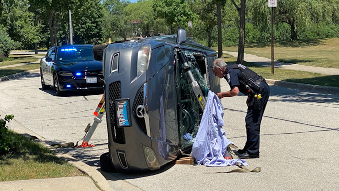 Police checking a car vs tree rollover crash on Heritage Drive Mount Prospect