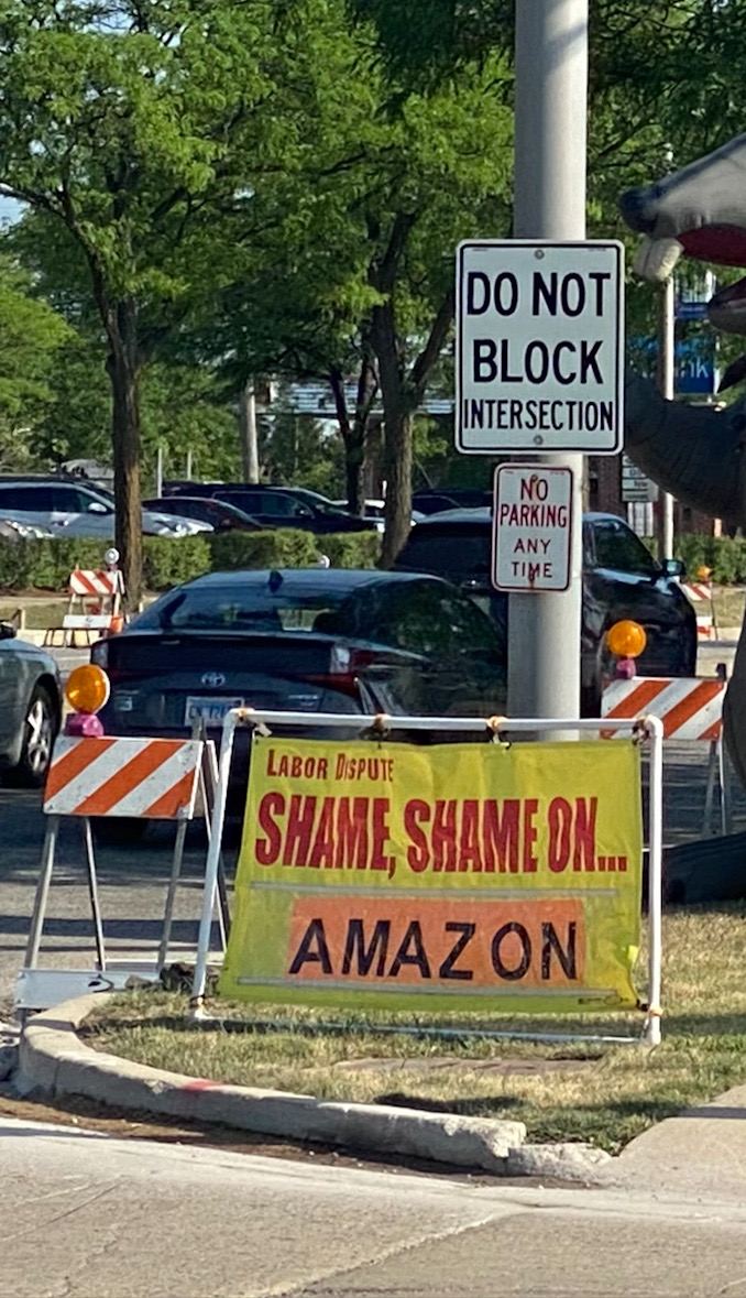 """Banner says, """"Labor Dispute: Shame, Shame on ... Amazon"""" at Arlington Heights Road and Lillian Avenue in Arlington Heights"""