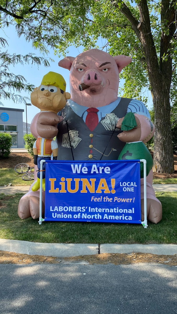 """Inflatable pig with cash with banner that says, """"We Are LiUNA! Local One Laborers' International Union of North America."""""""