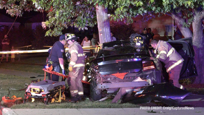 View toward the rear end of a Dodge Charger at a fatal crash scene shows firefighters working to free occupants of the Dodge Charger that hit a utility pole on Dugdale Road in Waukegan on Saturday, July 24, 2021