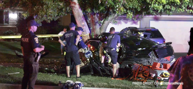 Fatal crash scene shows Dodge Charger stopped by a utility pole near residences and personal vehicles