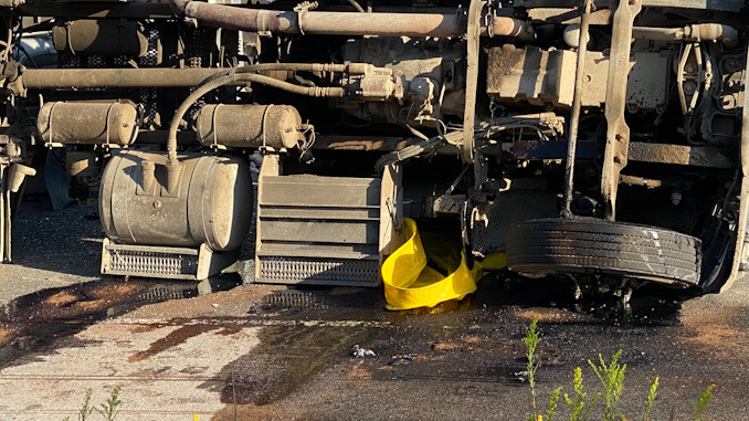 Rollover semi-trailer dump truck with a portable spill containment pool in place.