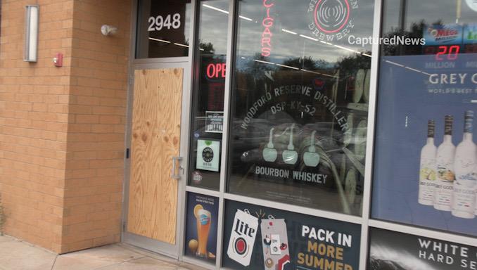 Front glass door boarded up at Esplanade Wine & Spirits on West Euclid Avenue near Salt Creek Lane in Arlington Heights